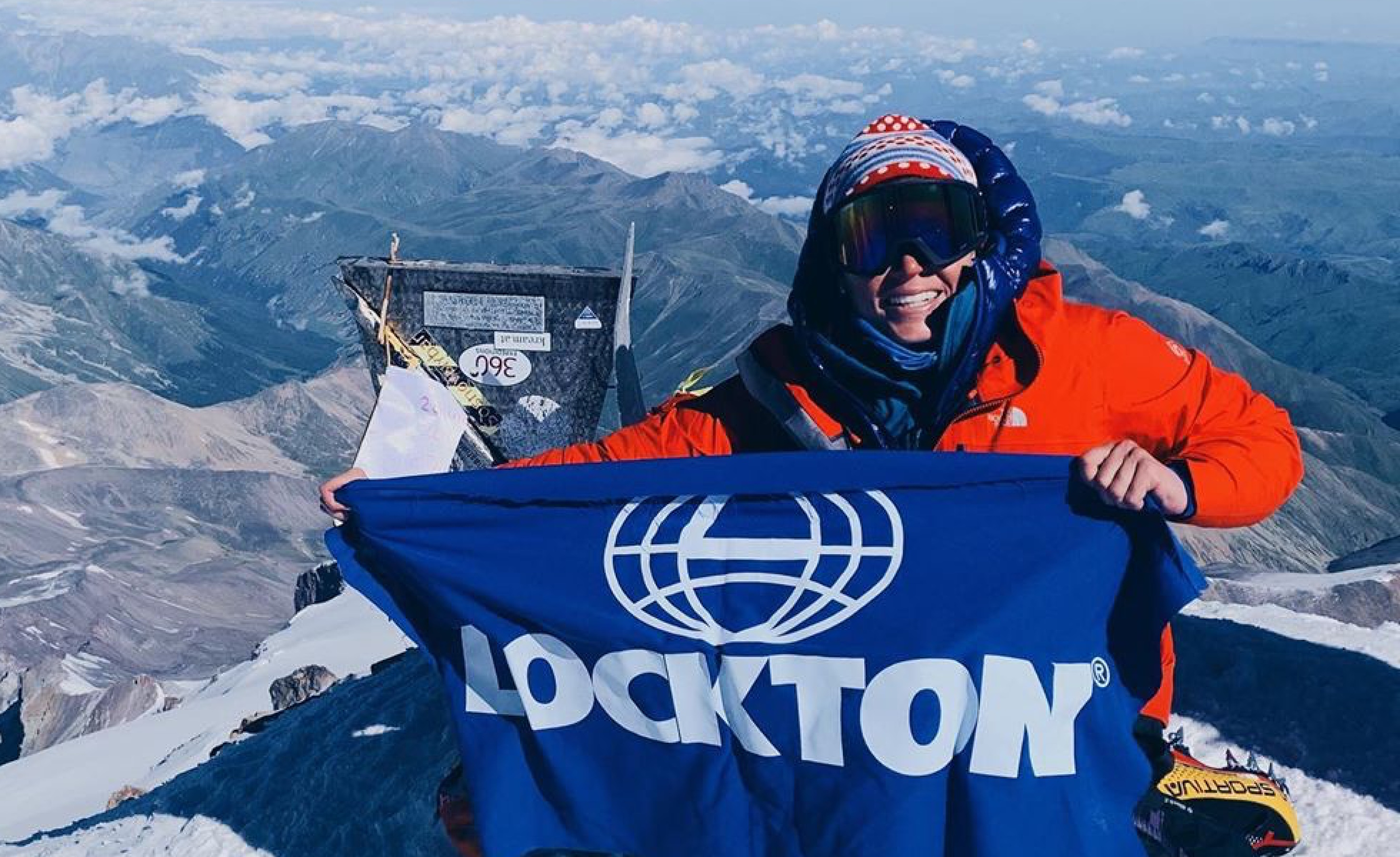 Lockton employee on the top of a mountain holding a Lockton flag
